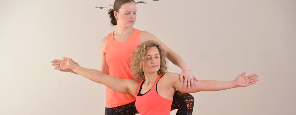 Achtsam korrigiert der Kursleiter die Pilates-Positionen